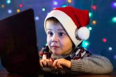 Pouco letra da escrita da criança a Santa Claus no laptop Rapaz pequeno com chapéu de Santa fotos de stock royalty free
