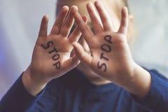 Pouco menina amedrontada mostra a parada da palavra escrita no braço As crianças são sujeitadas à violência e à publicação na cas imagens de stock