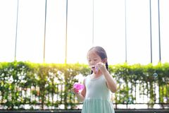 Pouco menina asiática bolhas de sabão de sopro no jardim exterior fotos de stock