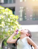 Pouco menina asi?tica bolhas de sab?o de sopro no jardim exterior imagens de stock royalty free