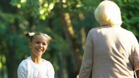Pouco menina ativa que fala emocionalmente à avó ao andar no parque, família video estoque