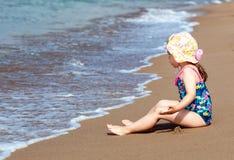 Pouco menina bonito da criança que senta-se na praia do mar fotografia de stock royalty free
