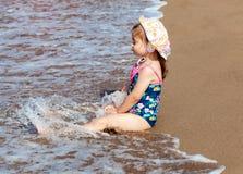 Pouco menina bonito da criança que senta-se na praia do mar foto de stock