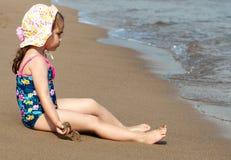 Pouco menina bonito da criança que senta-se na praia do mar imagem de stock