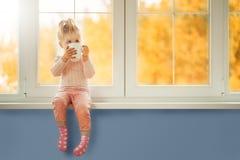 Pouco menina bonito da criança que senta-se pela janela que guarda o copo do cacau quente da bebida que aprecia o fundo da flores fotos de stock royalty free