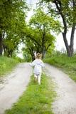 Pouco menina bonito do ruivo corre ao longo de uma estrada de terra com grama e risos fotografia de stock