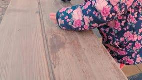 Pouco menina bonito em um revestimento cor-de-rosa colorido tira com giz em um banco perto do campo de jogos das crianças no parq video estoque