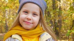 Pouco menina bonito no chapéu de néon azul da cor e no lenço amarelo está sorrindo no parque no outono filme