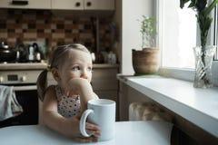 Pouco menina bonito que senta-se na tabela na cozinha imagem de stock