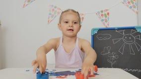 Pouco menina bonito que senta-se na tabela na sala de crianças que olha suas mãos, manchadas com pintura brilhante filme