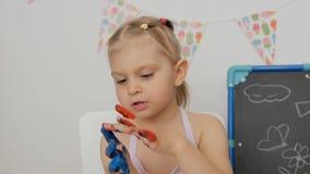 Pouco menina bonito que senta-se na tabela na sala de crian?as que olha suas m?os, manchadas com pintura brilhante video estoque