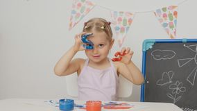 Pouco menina bonito que senta-se na tabela na sala de crian?as que olha suas m?os, manchadas com pintura brilhante vídeos de arquivo