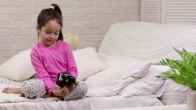 Pouco menina da crian?a ajusta o alarme na cama video estoque