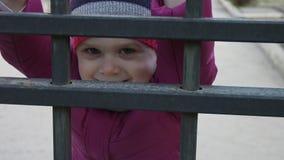 Pouco menina de sorriso 3-4 anos que escalam na cerca vídeos de arquivo