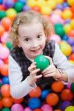 Pouco menina de sorriso que senta-se entre muitas bolas coloridas - foco raso nos olhos fotografia de stock royalty free