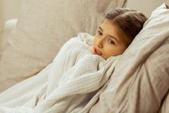 Pouco menina doente envolveu em uma cobertura que encontra-se na cama imagens de stock royalty free