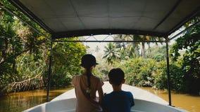 Pouco menina e menino felizes junto na vela do barco da excursão do safari ao longo do rio exótico da selva, exploradores novos n filme