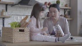 Pouco menina engraçada que senta-se na tabela que ajuda sua avó a cozinhar o bolo Posição superior da mulher perto da tabela com filme