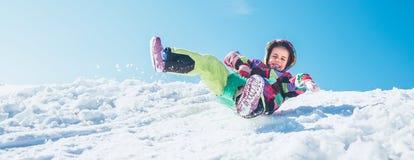 Pouco menina feliz desliza para baixo da inclinação da neve com céu azul imagem de stock royalty free