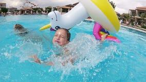 Pouco menina feliz e sua mamã que flutuam em um unicórnio inflável na associação video estoque