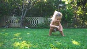 Pouco menina feliz que salta e que cai no quintal vídeos de arquivo
