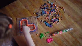 Pouco menina loura bonito que joga com mosaico colorido filme