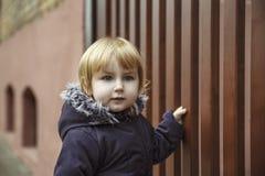 Pouco menina loura com olhos azuis olha algo curioso e fotos de stock royalty free