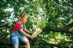 Pouco menina loura com um livro em uma ?rvore fotografia de stock royalty free