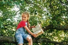 Pouco menina loura com um livro em uma ?rvore fotos de stock royalty free