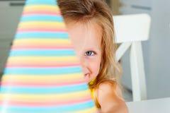 Pouco menina loura europeia bonito com os olhos azuis que guardam um chapéu colorido do partido na frente de sua cara Tiro próxim imagens de stock