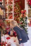 Pouco menina loura que olha as luzes do feriado e as decorações - v fotografia de stock royalty free