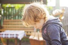 Pouco menina redheaded que joga na caixa de areia em um dia de verão ensolarado foto de stock royalty free