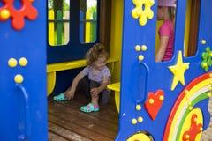 Pouco menina ruivo em uma casa de madeira para crianças no campo de jogos imagens de stock royalty free