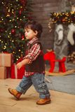 Pouco menino à moda que anda perto da árvore de Natal foto de stock royalty free