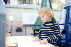 Pouco menino ?aucasian está olhando uma exposição em um museu científico imagem de stock royalty free