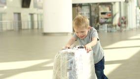 Pouco menino alegre que joga com uma mala de viagem no aeroporto na sala de espera