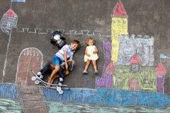 Pouco menino ativo da criança e desenho bonito do bebê da criança knight o castelo e a fortaleza com gizes coloridos no asfalto fotografia de stock royalty free