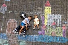 Pouco menino ativo da criança e desenho bonito do bebê da criança knight o castelo e a fortaleza com gizes coloridos no asfalto imagens de stock royalty free