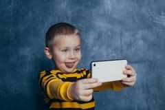 Pouco menino bonito com um telefone celular toma um selfie e mostra emo??es imagens de stock royalty free