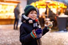 Pouco menino bonito da criança que come a salsicha alemão e que bebe o perfurador quente das crianças no mercado do Natal Criança fotos de stock royalty free
