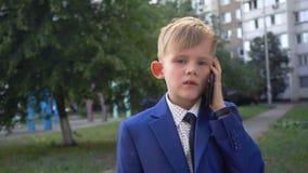 Pouco menino bonito em negociações de terno e de laço de negócio no telefone filme