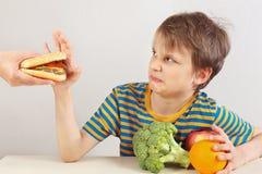 Pouco menino bonito em uma camisa listrada na tabela recusa o Hamburger em favor da dieta saudável no fundo branco fotos de stock