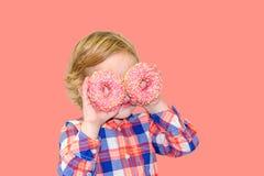 Pouco menino bonito feliz está comendo a filhós na parede cor-de-rosa do fundo fotos de stock