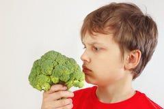 Pouco menino cortado em uma camisa vermelha com brócolis no fundo branco foto de stock royalty free