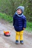 Pouco menino da criança de dois anos leva um caminhão do brinquedo em uma corda fotos de stock royalty free