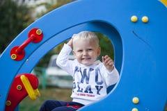 Pouco menino da criança de três anos que joga no campo de jogos Fotos de Stock Royalty Free