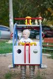 Pouco menino da criança de três anos que joga no campo de jogos Imagens de Stock Royalty Free