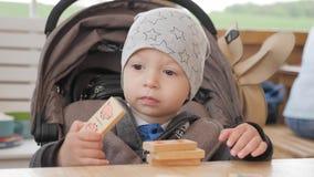Pouco menino da crian?a que joga com cubos de madeira em uma tabela em um caf? vídeos de arquivo