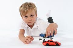 Pouco menino da criança que joga satisfyingly com seus brinquedos e que constrói uma torre dos carros imagem de stock