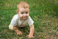 Pouco menino da criança treina suas habilidades de rastejamento A criança rasteja felizmente na grama verde imagens de stock